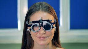 A happy female patient tries on am optical trial frame. A smiling woman tries on and removes a trial frame with ophthalmic lenses stock footage
