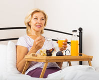 Happy female pensioner having   breakfast Royalty Free Stock Photos
