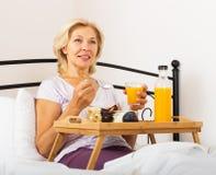 Happy female pensioner having   breakfast Royalty Free Stock Photos