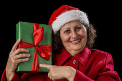 Happy Female Pensioner Pointing at Wrapped Gift. Smiling retired woman with red coat and Santa Claus hat. She is holding a wrapped green Christmas gift in her Royalty Free Stock Photography