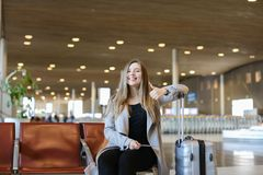 Happy female person sitting in airport hall with modern tablet near valise and showing thumbs up. Happy female person making video call by modern tablet in stock photos