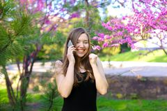 Happy female person speaking by smartphone in park near blooming trees. Happy female person speaking with boyfriend by smartphone in park near trees in blossom royalty free stock photos