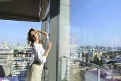 Happy female person standing at restaurant near window with cityscape background. Happy female person standing at restaurant near window with buildings in stock photos