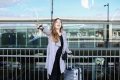 Happy female person stopping taxi with raised hand, valise and smartpone near airport. Concept of business trip and modern technology Royalty Free Stock Photography