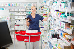Happy Female Pharmacist Updating Stock In Digital Royalty Free Stock Photography