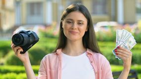Happy female photographer holding camera and dollars, hobby earning, income. Stock footage stock footage
