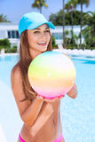 Happy female in the pool. Happy woman with ball in swimming pool, having fun on beach resort, enjoying summer activity, playing water game, vacation and Royalty Free Stock Images