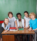 Happy Female Professor With Students At Desk Royalty Free Stock Photography