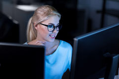 Happy female programmer working in the office. Decomposing the task. Smiling charming skilled programmer sitting in the office and using computers while working Royalty Free Stock Image