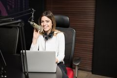Happy female radio broadcaster hosting a live show. Portrait of happy young hispanic female radio broadcaster sitting at desk with laptop and talking in mic Royalty Free Stock Photo