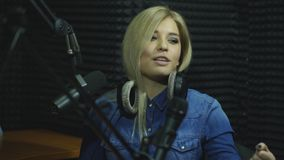 Happy female radio host broadcasting through microphone in studio stock footage