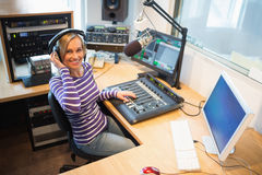 Happy female radio host at sound mixer desk in studio Royalty Free Stock Photography