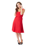 Happy female in red dress talks over mobile phone Stock Photography
