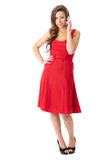 Happy female in red dress talks over mobile phone Stock Photo