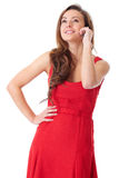 Happy female in red dress talks over mobile phone Royalty Free Stock Photo