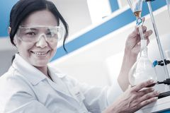 Happy female researcher smiling while pouring liquid into flask. Positivity is the key to success. Joyful mature scientist smiling into the camera while working stock photo