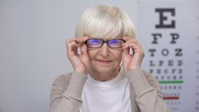 Happy female retiree putting on new spectacles and looking to cam, improvement. Stock footage stock video footage