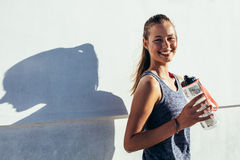 Happy female runner holding water bottle and smiling. Shot of happy female runner standing outdoors holding water bottle and smiling. Fitness woman taking a Stock Photo