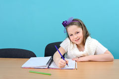 Happy female schoolchild doing her school work Stock Image
