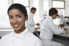 Happy Female Scientist In Laboratory. Portrait of happy female scientist with colleagues working in background Royalty Free Stock Photo