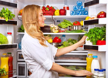 Happy female search something in the fridge. Fresh fruits and vegetables in the refrigerator, cooking diet food, fit and body care concept royalty free stock photos