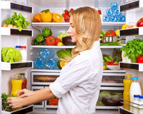 Happy female search something in the fridge. Fresh fruits and vegetables in the refrigerator, cooking diet food, fit and body care concept Stock Photo