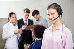 Happy Female Service Agent Standing At Call Center. Portrait of happy female service agent standing while team discussing in background at call center Stock Photos