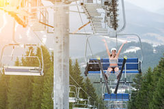 Happy female skier is sitting on ski lift, rising hand up and riding up to the top of the mountain. With ski equipment. Mountains, snowy slopes, forests on the stock photos