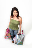 Happy female shopper. A young woman looks up as she holds on to several bags of shopping Royalty Free Stock Photos