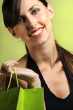 Happy female shopper. A happy, smiling young caucasian woman smiling and holding a shopping bag stock photo
