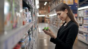 Happy female shopper searching for baby food in supermarket, yong mother mom in shop Royalty Free Stock Photos