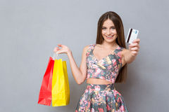 Happy female shopper showing a credit card and smiling Royalty Free Stock Images