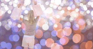 Happy female with shopping bags over bokeh Stock Image