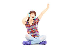 Happy female sitting on a floor and listening music Stock Images