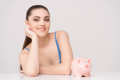 Happy female sitting at table with piggy bank. Royalty Free Stock Photo