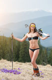 Happy female skier is enjoying warm spring, wearing swimsuit, boots and sunglasses Stock Photo