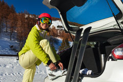Happy female skier putting on her ski boots. Close-up portrait of happy female skier putting her ski boots on, standing next to the car trunk Stock Photo