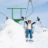 Happy female skier riding a lift. Royalty Free Stock Images