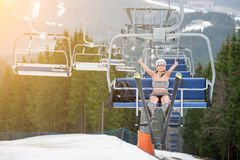 Happy female skier with skis is having fun on ski lift, rising hands and showing thumbs up Royalty Free Stock Photography