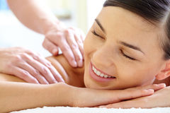 Happy female. Smiling female enjoying massage in spa salon royalty free stock photos