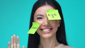 Happy female with sticky notes, learning body parts in English, education. Stock footage stock video