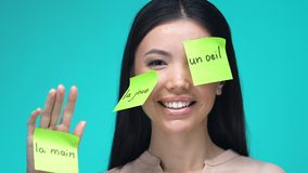 Happy female with sticky notes, learning body parts in French, education