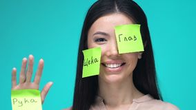 Happy female with sticky notes, learning body parts in Russian, education