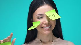 Happy female with sticky notes, learning body parts in Spanish, education