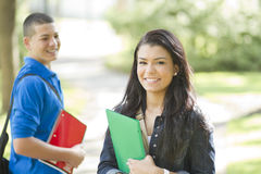 Happy female student. Two young students outdoors with folders and notebooks Royalty Free Stock Images