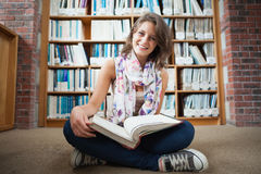Happy female student against bookshelf with a book on the library floor Royalty Free Stock Image