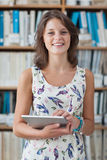 Happy female student against bookshelf holding tablet PC in library Stock Photography