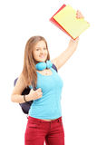 Happy female student with bag holding books and gesturing happin Stock Photography