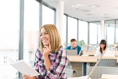 Happy female student with book in classroom Royalty Free Stock Photography
