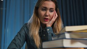 A happy female student in a denim shirt, surprised and concerned about a lot of books. A lot of work. Close-up. stock video footage